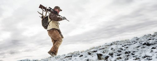 hunter carrying rifle over shoulder in wilderness