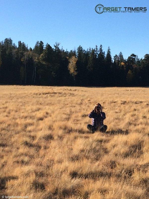 Sitting in a field Glassing through Carson binoculars.