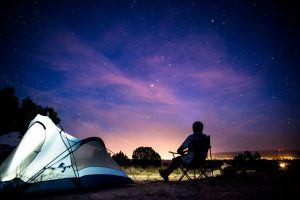 Man sitting in camp site gazing at the stars