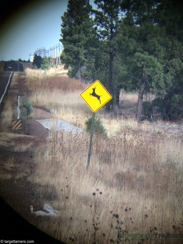 A deer crossing road sign as seen through binoculars