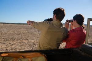 rear-view-of-couple-looking-through-binoculars-on-safari