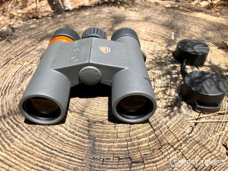 Maven C.2 7x28 binoculars sitting on a tree stump